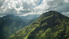 Stunning time lapse of green mountains as clouds move to bathe them in sunlight - stock footage
