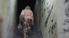 Woman climb a series of stairs, emerging from an underpass Stock Footage