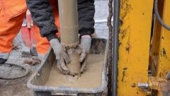 Worker strikes with a hammer mill head for it to fall from accumulated material Stock Footage