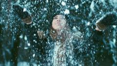 Сheerful young adult attractive Caucasian girl throwing snow in the air Stock Footage