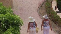 Two grandmothers dressed alike walking together top view Stock Footage