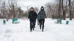 Group of people running on the snow alley, slow motion Stock Footage