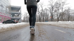 Young woman running on the snow road near the park, slow motion - stock footage
