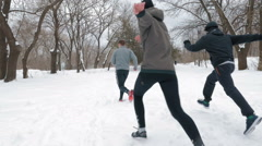 Group of people running in snowdrift and having fun,slow motion Stock Footage