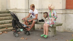 Glamorous senior lady sitting on the bench, father and kid having rest in park Stock Footage