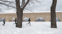 Group of people running on the snow alley between trees, slow motion Stock Footage