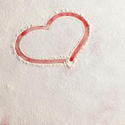 Valentine love red heart shape in snow on red background. - stock photo