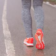 Sporty Runner feet running on the wet road. Stock Photos