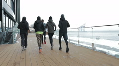 Group of people running on the snow sea berth, slow motion - stock footage