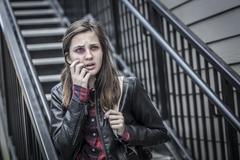 Young Badly Bruised and Frightened Girl with Backpack on Staircase. Stock Photos