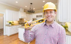 Smiling Contractor with Level Wearing Hard Hat Standing In Custom Kitchen. Stock Photos