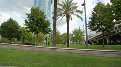 Modern skyscraper in resort city, park with exotic trees outside office building Stock Footage