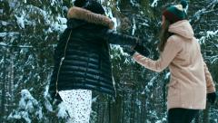 Two cheerful young adult attractive Caucasian girls having fun in winter forest Stock Footage