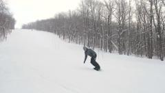 Snowboarder carves while snowboarding down a slope Stock Footage