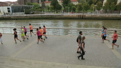 People running at riverside, healthy lifestyle promotion campaign in big city Stock Footage
