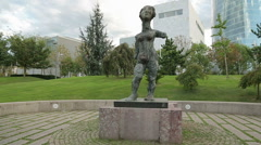 Strange female statue exhibited in the park in front of modern business center Stock Footage