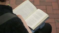 Person enjoying bestseller book in the park, reading text on paper pages Stock Footage