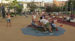 Kids of different age playing on playground roundabout, happy children smiling Arkistovideo