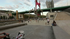 Many tourists strolling near huge spider sculpture, summer evening in Bilbao Stock Footage