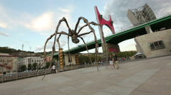 Tourists viewing huge Maman spider sculpture, sightseeing tour around Bilbao Stock Footage