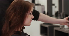 An attractive woman looking into the mirror after having her haircut done. Stock Footage