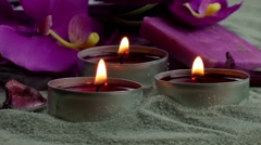 Candles and orchid flower on the sand - stock footage