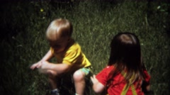 1971: Baby brother and sister clowning around in long grass. - stock footage