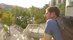 Male tourist enjoying amazing balcony view in resort city, happy guy on vacation Stock Footage