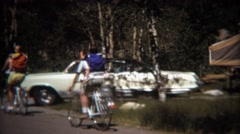1971: Family bike ride ending at popup camper outdoor site. Stock Footage