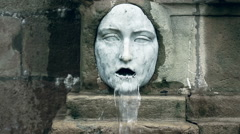 Horizontal pan of two marble fountain sculptures with horrifying grotesque faces Stock Footage