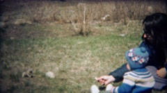 1971: Mother and baby son feed wild chipmunk rodent animal. Stock Footage