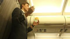 Steward on the plane shows how to use an oxygen mask Stock Footage