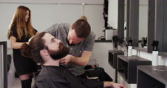 Hipster having his beard trimmed at his local barber shop. Shot on RED Epic. Stock Footage