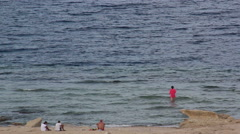 four people spend time on the beach watching the sea swim talk - stock footage