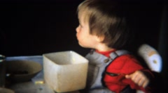1971: Toddler boy eats cereal from square tupperware bowl. Stock Footage