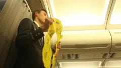 Steward on the plane shows how to use a life jacket Stock Footage