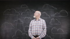 4K Portrait of thinking man standing in front of blackboard with clouds - stock footage