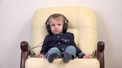 Stock Video Footage of Little child with headphones relaxing on comfortable armchair, listening music