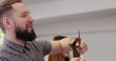 Friendly salon owner chatting with his client while giving him a hair cut. - stock footage