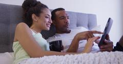 Early morning couple looking at tablet computer in bed and drinking coffee Stock Photos