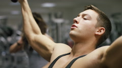 Handsome man working out in the gym doing lateral pulldowns, in slow motion Stock Footage
