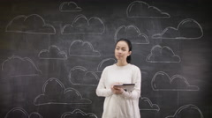 4K Portrait of thinking woman standing in front of blackboard with clouds - stock footage