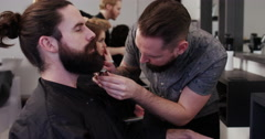 Barber using clippers on clients beard in barber shop. - stock footage