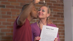 Just bought a house - Man kisses wife holding deed and keys - stock footage