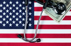 Financial medical concept with stethoscope and money on the United States fla - stock photo