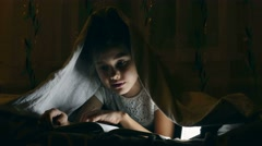 Girl reading book with flashlight under covers at night Stock Footage