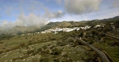 4K Aerial, Flight over andalusian village, surrounded by massive mountains, Spai - stock footage