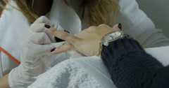 Beautician with brush painting nails of woman in beauty salon,manicure,close up. - stock footage