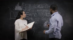 4K Academic man & woman writing math formulas on blackboard & discussing ideas - stock footage