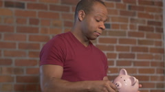 Money Worries - African American Man Holding Piggy Bank Arkistovideo